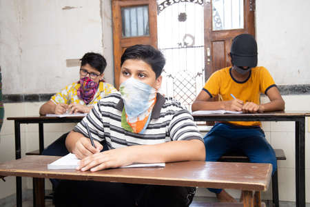 Indian Students wearing face masks maintaining social distancing at a classroom as school reopen during covid19 pandemic.