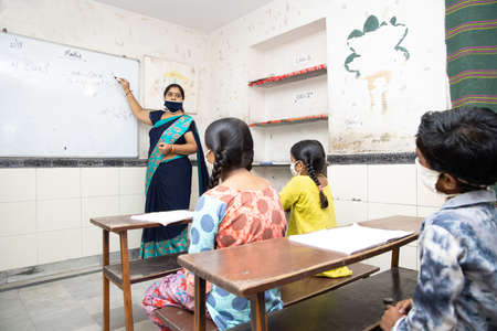 Indian teacher and students wearing face masks maintaining social distancing study in classroom back at school during covid19 pandemic.