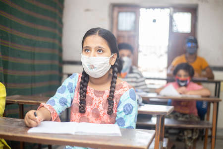 Indian Students wearing face masks sitting with social distancing at a classroom as school reopen during covid19 pandemic.