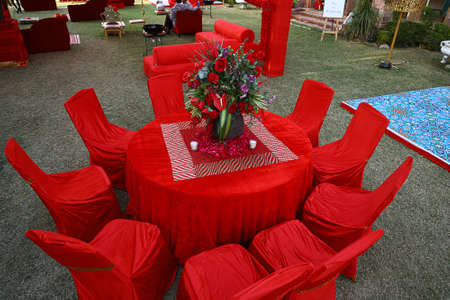 Organized red table and chairs decorated with flower centerpiece, luxury sitting arrangement ready for the guests on a grassland or backyard