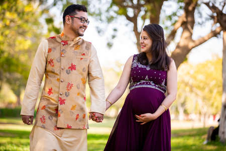 Happy asian indian pregnant woman with her husband in walking outdoor in a park or garden, smiling cheerful young parents looking at camera expecting baby. 版權商用圖片