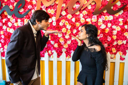 Young indian couple in love looks at each other blowing kiss with hand or flying kiss against flower background. new year or valentines day concept. Standard-Bild