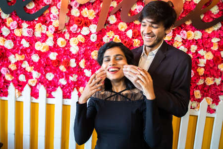 Young happy cheerful indian couple in love have fun together, man pinching cheeks of his girlfriend against floral background, enjoy life, new year or valentines day.
