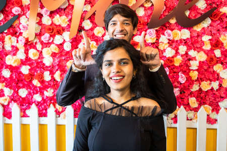 Young happy cheerful indian couple in love have fun indoor against floral background, boyfriend girlfriend relationship, new year or valentines day. Standard-Bild