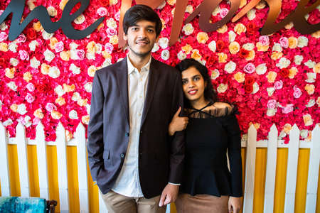 Portrait Of Young happy indian couple in love standing against floral background, boyfriend girlfriend relationship, new year or valentines day. Standard-Bild