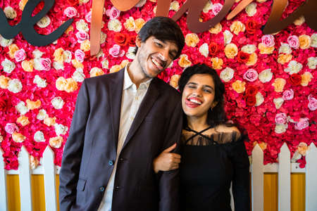 Young happy cheerful indian couple in love have fun together against floral background, boyfriend girlfriend relationship, enjoy life, new year or valentines day.