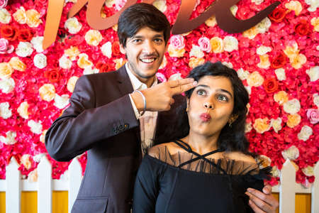 Young happy cheerful indian couple in love have fun together, man making shooting gun hand gesture, new year or valentines day concept. Standard-Bild