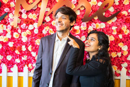 Young happy cheerful indian couple in love have fun indoor against flower background, boyfriend girlfriend relationship, new year or valentines day.