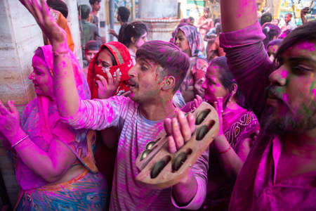 Jodhpur, rajastha, india - March 20, 2020: indian people dancing celebrating holi festival, face covered with colored powder.