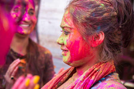 Jodhpur, rajastha, india - March 20, 2020: Young indian woman celebrating holi festival, face covered with colored powder.