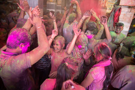 Jodhpur, rajastha, india - March 20, 2020: indian people dancing celebrating holi festival throw colored powder. top angle, background.