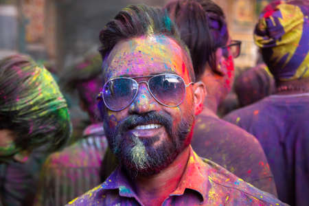 Jodhpur, rajastha, india - March 20, 2020: Portrait of indian men smiling wear goggles celebrating holi festival, face covered with colored powder.
