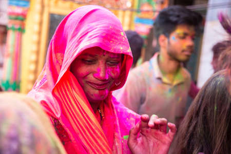 Jodhpur, rajastha, india - March 20, 2020: indian woman wearing saree celebrating holi festival, face covered with pink colored powder. Editorial