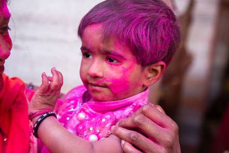 Jodhpur, rajastha, india - March 20, 2020: indian cute little kid face covered with pink colored powder. celebration of holi festival Editorial