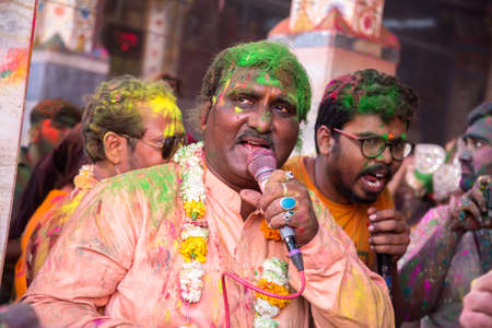 Jodhpur, rajastha, india - March 20, 2020: indian people singing and dancing while celebrating holi festival, face covered with colored powder.