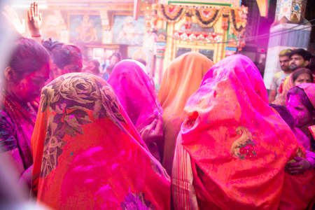 back view of indian women wearing saree celebrating holi festival with colored powder. background Editorial