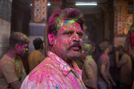 Jodhpur, rajastha, india - March 20, 2020: indian man celebrating holi festival, face smeared covered with colored powder.