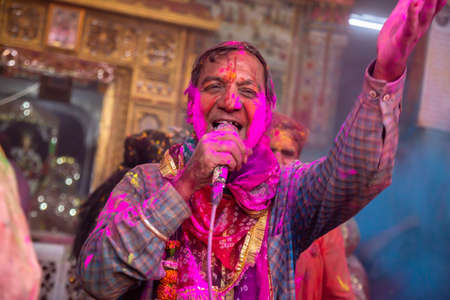Jodhpur, rajastha, india - March 20, 2020: indian people singing and celebrating holi festival , face covered with pink colored powder.