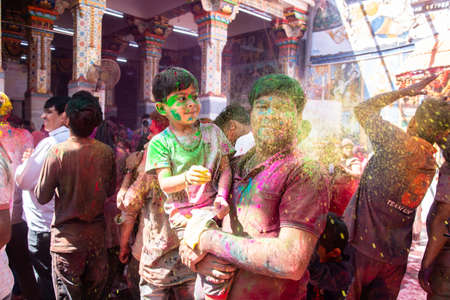 Jodhpur, rajastha, india - March 20, 2020: Young indian father and son celebrating holi festival, closeup of face covered with colored powder.