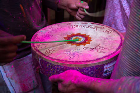 Jodhpur, rajastha, india - March 20, 2020: closeup of people hand playing indian drum with sticks during holi festival, covered with color powder, background..