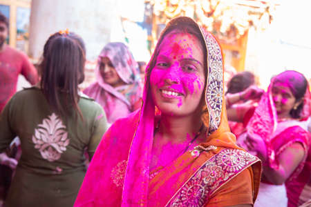 Jodhpur, rajastha, india - March 20, 2020: Young indian woman wearing saree celebrating holi festival, face covered with pink colored powder. Editorial