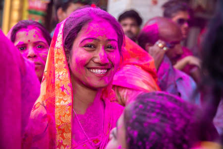 Jodhpur, rajastha, india - March 20, 2020: smiling Young indian woman wearing saree celebrating holi festival, face covered with pink colored powder. Editorial