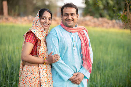 Happy indian rural farmer couple in agricultural field.