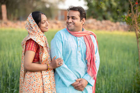 Happy indian rural farmer couple in agricultural field looking at each other laughing. Standard-Bild