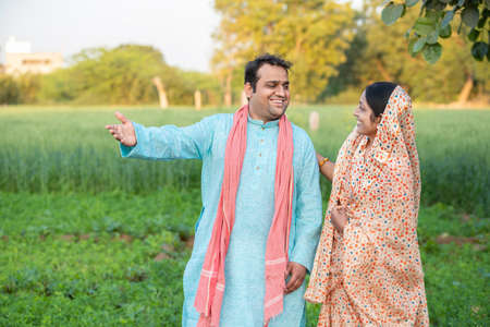 Happy young indian rural farmer couple in agricultural field looking at each other laughing. Standard-Bild