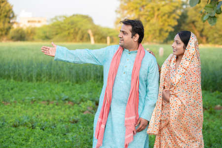 Happy young indian rural farmer couple in agricultural field looking at each other laughing. copy space to write text. man wearing kurta and woman wearing saree, Standard-Bild