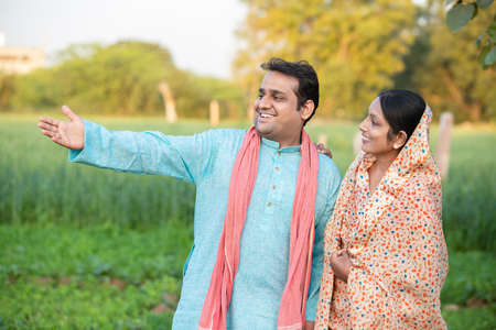 Happy young cheerful indian rural farmer couple in agricultural field, man showing crop to her wife. Standard-Bild
