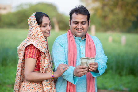 Happy Indian farmer couple counting rupees note at agriculture field, Man holding money. Standard-Bild