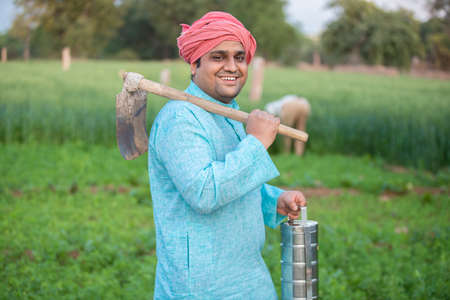 Portrait of traditional indian farmer couple or labor worker in agriculture field holding tiffin lunch box and pretail garden spade / shovel tool.