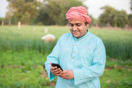 Young happy indian farmer worker using smartphone while standing in agriculture green field, internet banking, 5g network technology concept, male wearing traditional kurta outfit. Standard-Bild