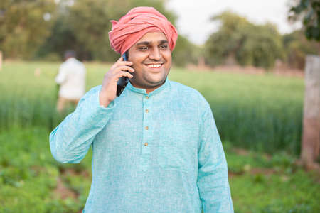 Young happy indian farmer worker talking on phone while standing in green field, agriculture and technology concept, male wearing traditional kurta outfit, copy space to write text.