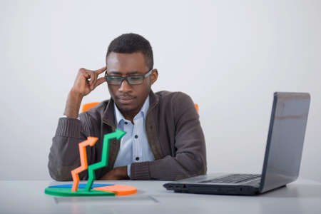 african american man: Businessman in an office looking at some arrows and thinking