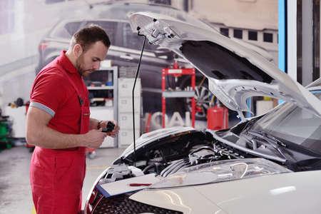 Man aan het werk in een garage die auto repareert Stockfoto