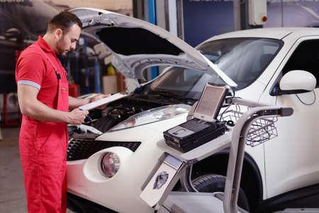 Mechanic repairing a car in garage Stock fotó