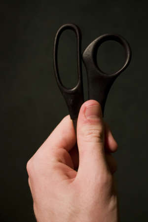 grasp: Hand Holding Black Scissors against a background Stock Photo