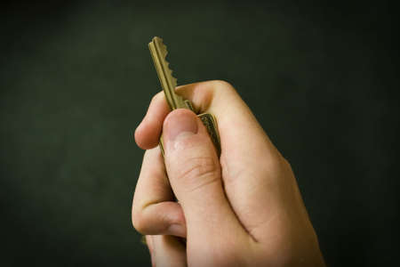 grasp: Hand Holding a Key against a black background Stock Photo