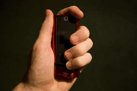 grasp: Hand Holding a cell phone against a black background Stock Photo