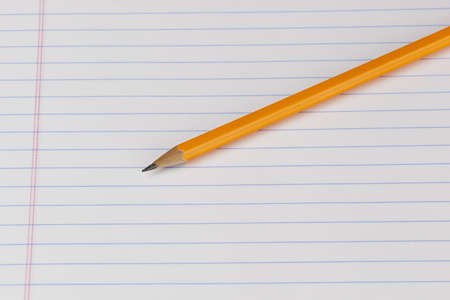 A yellow pencil on notebook paper photo