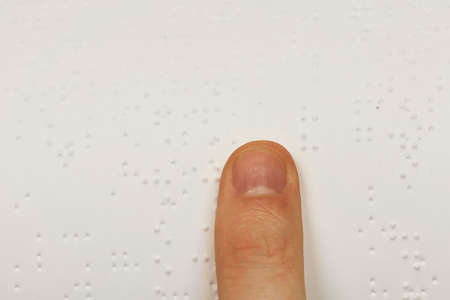 A finger on a book of braille photo