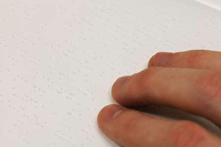 Een hand op een braille-boek