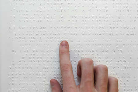 A hand on a braille book photo
