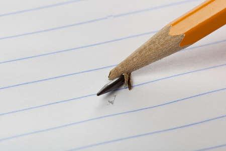 ノートブック紙の上の壊れた黄色の鉛筆