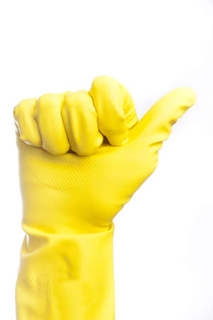 disinfect: A yellow cleaning glove against a white background