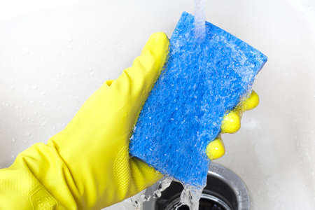 Washing a white plate with a sponge and rubber gloves photo