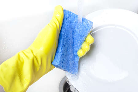 Washing a white plate with a sponge and rubber gloves Stock Photo - 9864729
