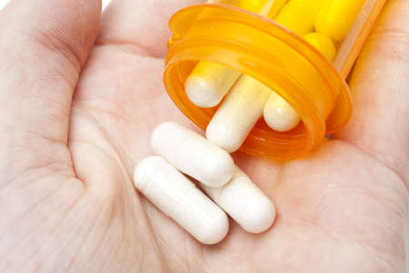 White pills pouring into a persons hand photo